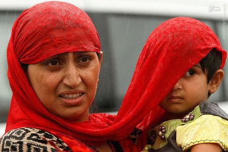 زن کشمیری با روسری خود از خیس شدن کودکش زیر باران جلوگیری میکند