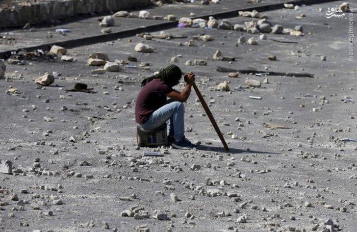 یک معترض فلسطینی در محل درگیری با رژیم صهیونیستی نشسته است