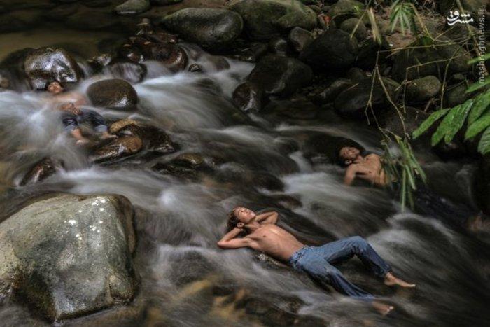 دانش آموزان نوجوان مالزیایی در روز تعطیلی مدارس خود را در رودخانه خنک کردند