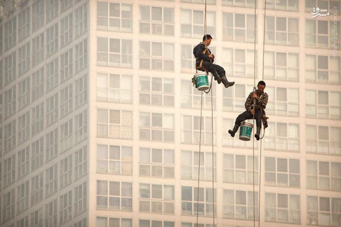 کارگران در حال شستشوی پنجره های آلوده در پکن چین