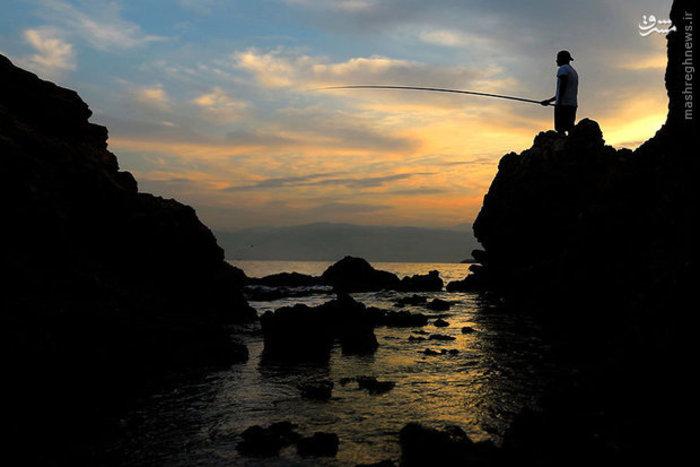 یک مرد در سواحل لبنان ماهیگیری میکند