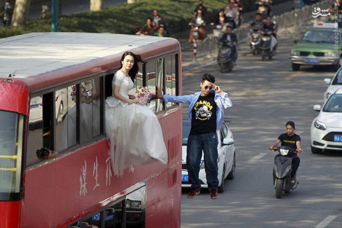 شعبده باز چینی که کنار اتوبوس دو طبقه در هوا معلق است