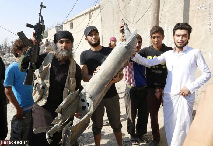 ترورست داعشی تکه ای از یک هواپیما که ادعا شده متعلق به ارتش سوریه است را در دست گرفته است.