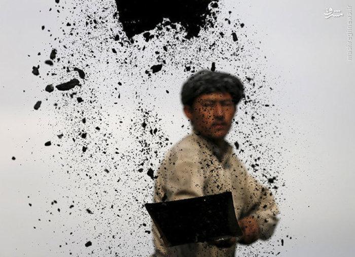 کارگری در حال خالی کردن زغال سنگ های یک کامیون در کابل پایتخت افغانستان