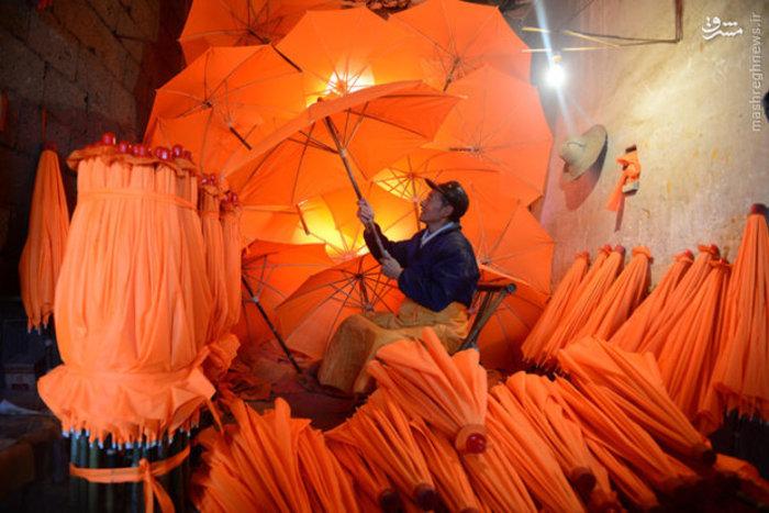 کارگر کارخانه ای در چین در حال بررسی سالم بودن چترها