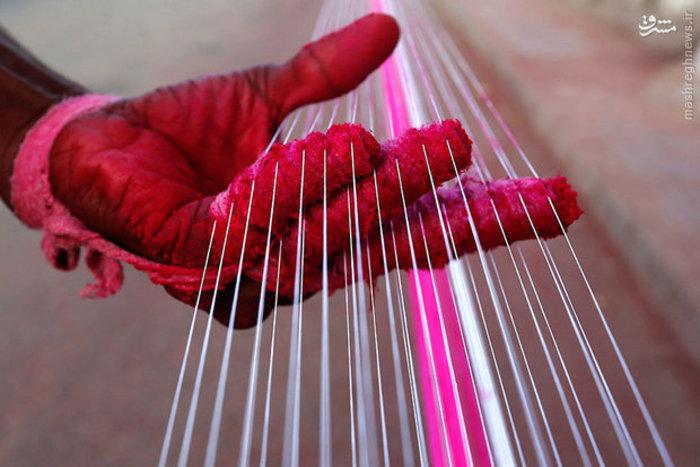 کارگر تولید بادبادک، رشته های نخی را رنگ میکند
