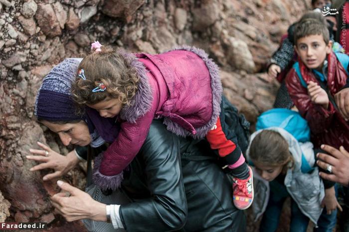 عبور زن مهاجر با فرزند خودش از صخره ای که از کنار دریای اژه می گذرد. 11 اکتبر 2015