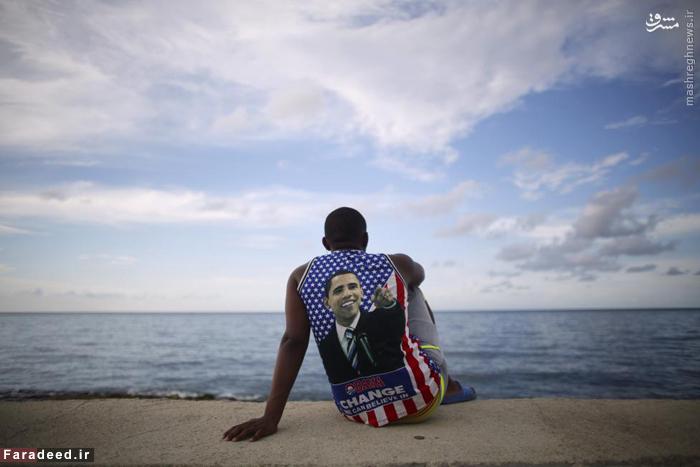 دانشجوی پزشکی با پوششی از شعار و عکس اوباما که وعده ی تغییر داده است در حوالی سفارتخانه ی آمریکا هاوانا کوبا. 14 آگوست 2015