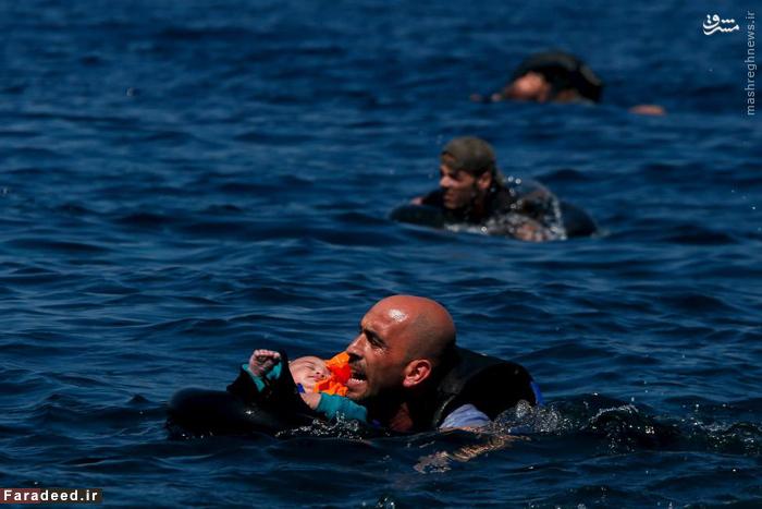 پناهنده سوری بعد از واژگونی قایق مهاجران سعی میکند فرزندش را به جزیره یونانی لزبوس برساند. 12 سپتامبر 2015