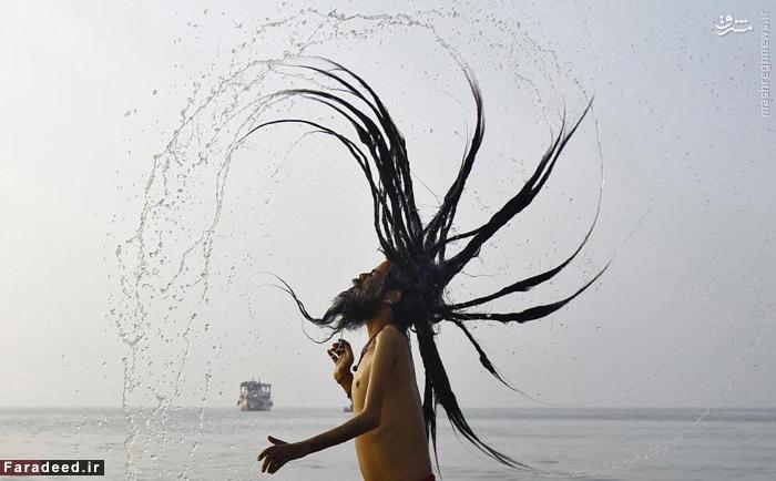 مرتاض هندو در حال آب تنی کردن، در محل برخورد رودخانه ی گنگ در سواحل بنگال در جشنواره ی
