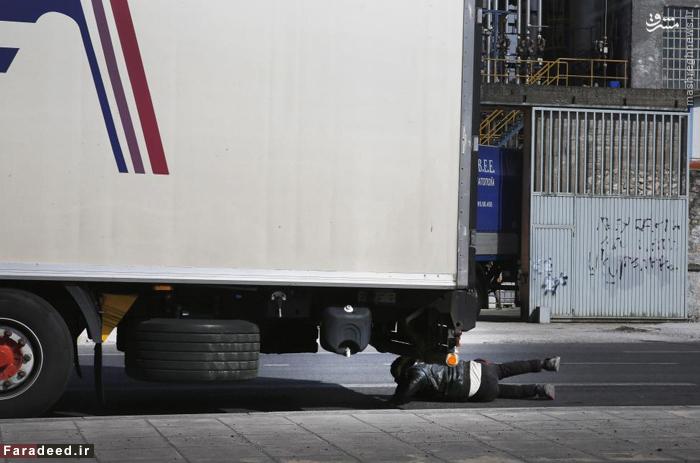 مهاجر آفریقایی در یونان در حال مخفی شدن زیر کامیون. آوریل 2015