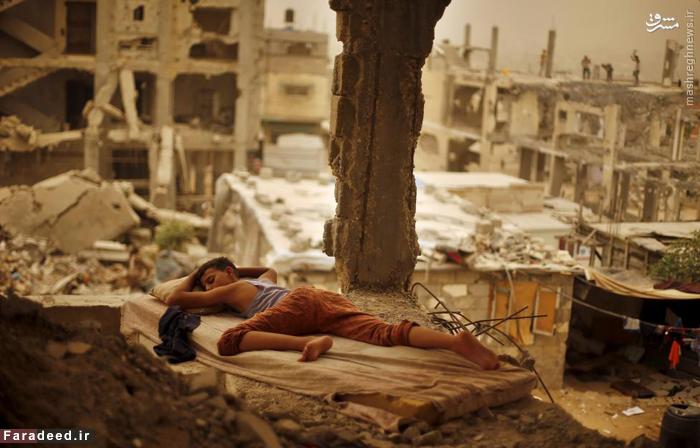 نوجوان فلسطینی در ویرانههای خانه اش که توسط موشک های اسرائیل در جنگ 50 روزه به این روز افتاده به خواب رفته است. 8 سپتامبر 2015