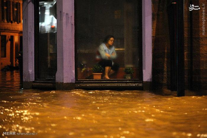زنی هنگام وقوع سیل در رستوران چینی در انگلیس نشسته است